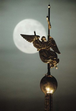 Gold-plated ahgel on spire of St.Peter and Poul cathedral in St.Petersburg against the background of the moon.