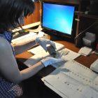 Хранитель работает с коллекцией монет, находящихся в специальных бумажных пакетах